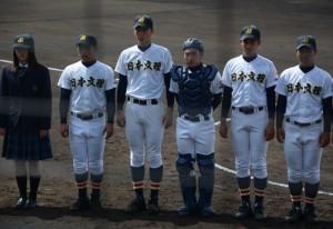 第一試合前にバックネット前に整列、場内アナウンスで紹介を受ける飯塚投手(左から3人目)ら日本文理の選手